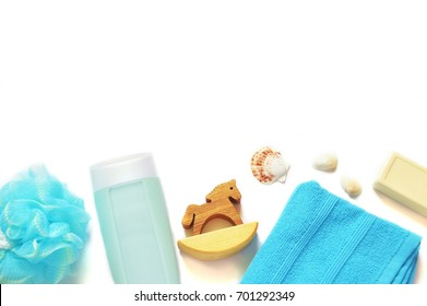 Flat lay organic bath products. Blue sponge puff, shampoo bottle, wooden toy horse, baby soap on a white background. Natural cosmetics for hair and skin care. Mockup for design site