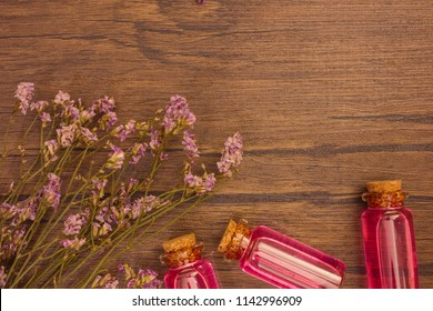 Flat lay organic essential oil and flower with copy space on brown wooden background