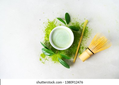 Flat lay of organic green tea Matcha powder with Japanese tools Chasen bamboo whisk, Chashaku spoon and bowl for brewing on light background with copy space.