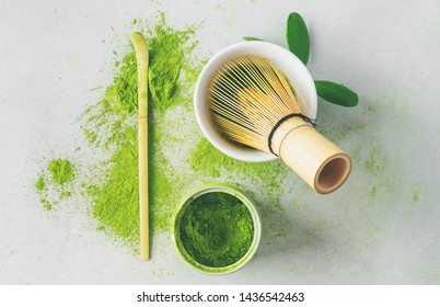 Flat lay of organic Japanese green tea and tools Chasen bamboo whisk, Chashaku spoon and bowl for brewing background with copy space.
