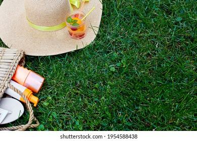 Flat Lay Outdoor heller Sommerurlaub oder Reise Lifestyle-Konzept mit Strohsack, Hut, Flip Flops, Limonade und Sonnencreme Spray auf Grashintergrund, Draufsicht, Kopienraum.