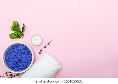 Flat lay overhead composition with organic sea salt with lavender, towel, candles and dry lavender twigs on pink background with copy space for your text. Spa and wellness concept.
