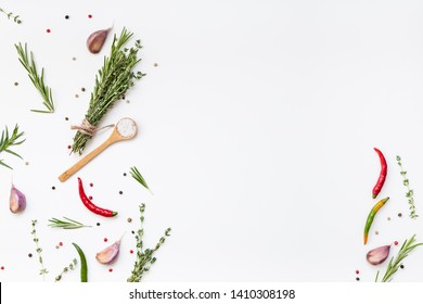 Flat lay overhead top view of greens herbs and spices on white background with copy space. Menu frame design food pattern background with cooking ingredients