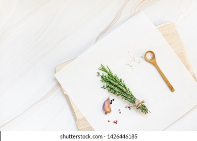 Flat lay overhead top view of greens herbs and spices on white marble background with copy space. Menu frame design food pattern background with cooking ingredients