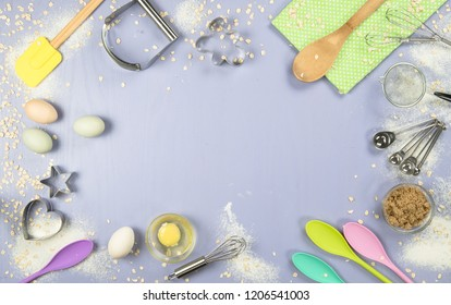 Flat lay or overhead view of baking tools and ingredients in pastel tones on a purple board