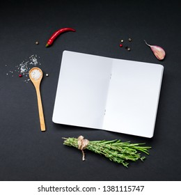 Flat lay overhead view blank notebook pages mockup text space invitation card on black background with greens herbs and spices. Menu or recipe book or food blog design with cooking ingredients