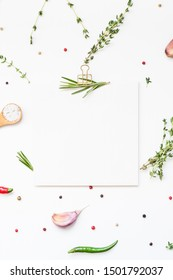 Flat lay overhead view blank recipe paper page with clip mockup text space invitation card on white background with greens herbs and spices. Menu recipe book food blog design with cooking ingredients