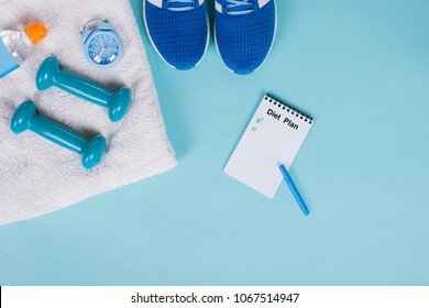 Flat lay a pair of sport shoes, a bottle of water, dumbbells on a blue surface background. Concept healthy lifestyle, sport and diet. Focus is only on the sneakers. Sport equipment.