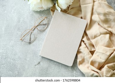 Flat lay paper notebook, eyeglasses, peony flowers and beige cloth on stone background. Top view girl home office desk with elegant accessories. Modern feminine workspace concept