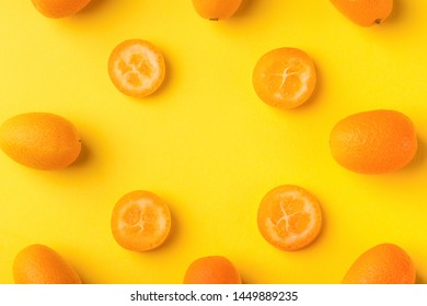 Flat lay pattern of fresh kumquats on a yellow  background. Top view, kumquats mock-up