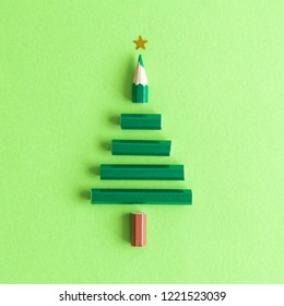 Flat lay of pencil in form of Christmas tree abstract on pastel green background.