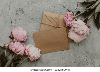 Flat lay peony flowers with craft card and envelope. Beautiful flower composition. Wedding invitation