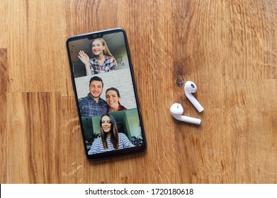 Flat lay of a phone lays on the wooden table, a few of people profiles on the screen, airpods headphones near. App for video communication on phone screen