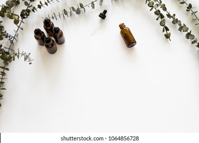 Flat lay photo of amber dropper bottles and eucalyptus on a white background