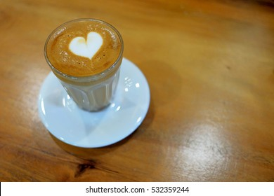 Flat lay photo  of designed value added latte coffee in a cup with heart milk cream on top on wood table served in the morning or coffee time with very romantic environment for friends or lovers time