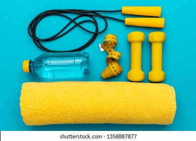 flat lay photo of fitness equipment over turquoise blue backgound. top view of yellow street workout objects. dumbells, jump rope, towel and other objects in oder, ready to be used