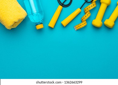flat lay photo of fitness equipment over turquoise blue backgound. top view of yellow street workout objects. yellow fitness objects on the blue background with some copy space