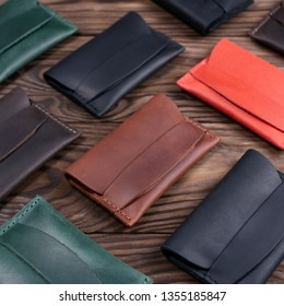 Flat lay photo of five different colour handmade leather one pocket cardholders. Red, black, blown, ginger and green colors. Stock photo on wooden background.