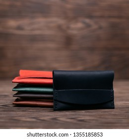 Flat lay photo of five different colour handmade leather one pocket cardholders. Black cardholder on foreground. Red, black, blown, ginger and green colors. Stock photo on wooden background.
