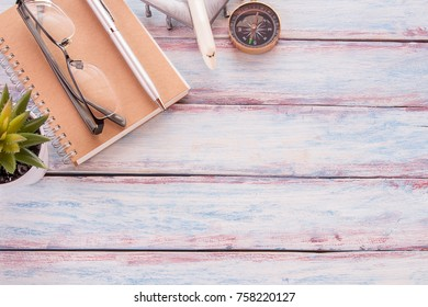 Flat lay photo with notebook,glasses,airplane toy,compass, pen and cuctus flower on wooden table background. Top view with copy space for design