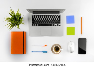 Flat lay photo of office desk with laptop, notebook and coffee