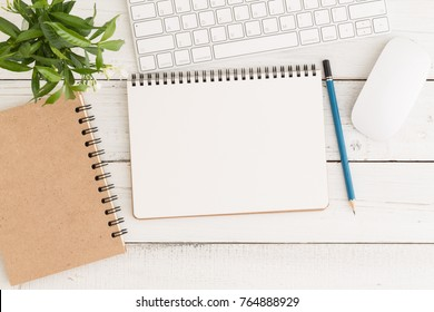 Flat lay photo of office desk with mouse and keyboard,Empty open notebook on white wood table top view