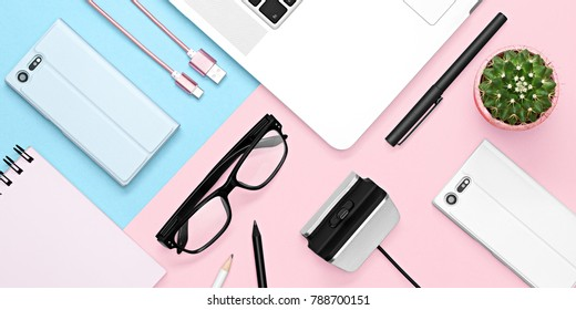 Flat lay photo of office desk with case for phone and tablet, notebook, tea mug, pencil and pen, cactus, on pink and blue background