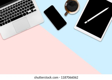 Flat lay photo of office table with laptop computer, digital tablet, mobile phone and accessories. on modern two tone (blue and pink) background. Desktop office mockup concept.