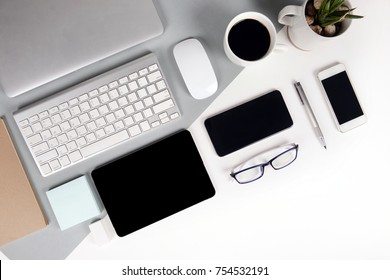 Flat lay photo of Office table with keyboard, notebook, digital tablet, mobile phone, Pencil, eyeglasses  on modern two tone (white and grey) background. Desktop office mockup concept.