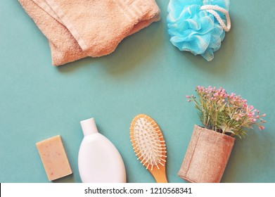 Flat lay photo still life cosmetic products photo for beauty blog. Morning routine for personal care. Top view natural organic bath products. Beige terry towel, blue sponge, brown handmade soap, comb