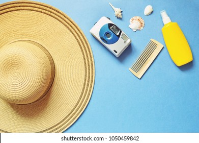 Flat lay photo sun hat, vintage camera, wooden comb, yellow sunscreen bottle and seashells on a blue background. Women's accessories for for beach holidays