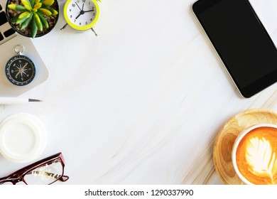 Flat lay photo in top view of business accessories, mobile, alarm clock, laptop, coffee, glasses and compass on white marble table with free copy space for text. Business and technology concept.