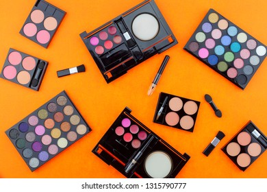 Flat lay photo of various makeup brush, eyeshadow and cosmetics on colorful orange paper background.