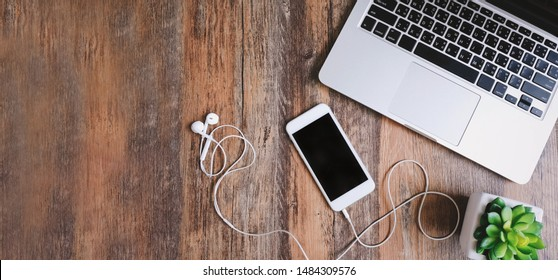 Flat lay photo of workspace desk with laptop, smartphone, earphones and green plant with copy space wooden background, banner for website header and design for text