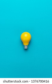 flat lay photo of yellow bulb on turquoise blue backgound. top view of lightbulb in the center of the shot with vertival orientation. minimalist picture of yellow painted electric lamp with copy space