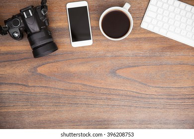 Flat lay of a photographers desk with a digital camera, a smartphone and some coffee with plenty of copy space