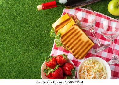 Flat lay. Picnic on the lawn with a veil, red wine with glasses, sandwiches, strawberries, and fresh salad, healthy and tasty food, The concept of a picnic, summer and rest