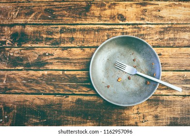 Flat lay picture of a dirty plate after having eaten the dish on a grungy wooden table with copy space.