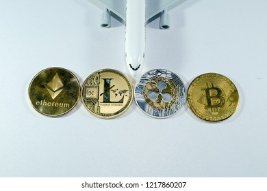 A flat lay picture of Etherum coin, Lite coin, Ripple coin and Bitcoin. Traveling will be easy with crypto currency.
