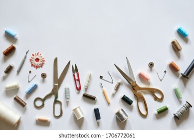 Flat lay picture of sewing accessories isolated on white background. Scissors, colorful threads and pins, ready for handmade usage.