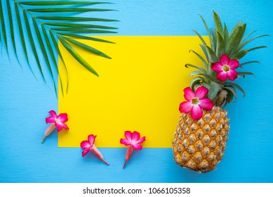Flat lay of pineapple, flowers, palm leaf on yellow and blue background with copy space, tropical summer holiday vacation, wedding invitation party concept