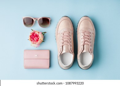 Flat lay pink feminine accessories on blue background.