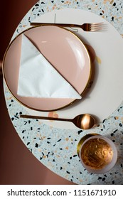 Flat lay of pink gold bronze cutlery pink plate and a glass of water with ice on a white terrazzo round table