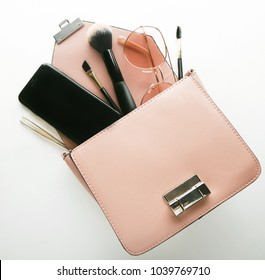 Flat lay of pink leather woman bag open out with cosmetics, acce