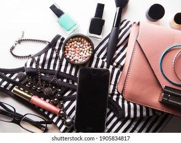 Flat lay of pink leather woman bag with cosmetics, accessories and smartphone on white background