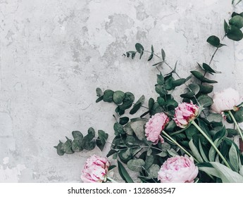 Flat lay pink peonies on stone background with eucalyptus . Creative floral image. Happy mother's day. International womens day. Greeting card mockup