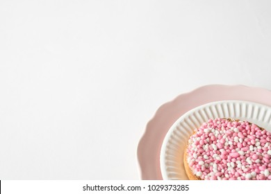 flat lay pink plate with crispy rusk with traditional Dutch food muisjes, aniseed, announcement that a baby girl is born. white background, space for text.