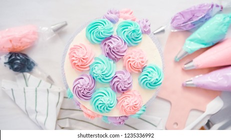 Flat lay. Piping pastel color buttercream rosettes on a white cake to make a unicorn cake.