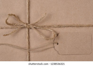 Flat lay plain brown paper wrapped Christmas Present with twine and tag with the words Merry Christmas.
