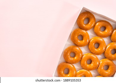 Flat lay. Plain glazed store-bought doughnuts in a white paper box.